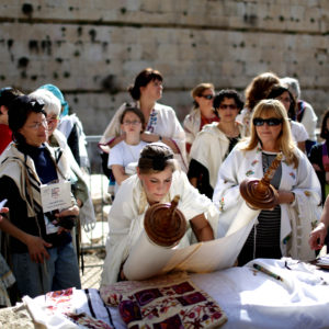 epa03619945 An Israeli Jewish woman lays down a Torah scroll (C) during a prayer session near the Western Wall in the Old City of Jerusalem, Israel, 12 March 2013. The prayers, attended by hundreds of women, marked the beginning of the Hebrew month of Nisan.  EPA/ABIR SULTAN